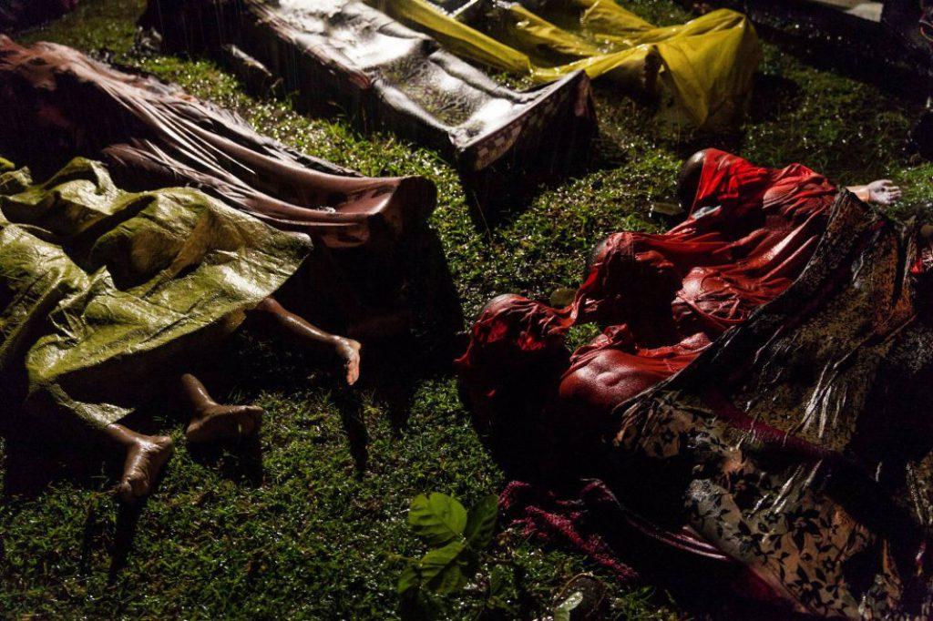 Los cuerpos de refugiados rohingya cubiertos en el suelo después de que el barco en el que huían alrededor de 100 personas desde Myanmar se hundiera antes de alcanzar la costa de Bangladés, el 28 de septiembre de 2017. Solo 17 personas sobrevivieron. Fotografía nominada en las categorías Photo of the Year y a 'Noticias generales' en el World Press Photo, del fotógrafo Patrick Brown de Panos Pictures para Unicef.