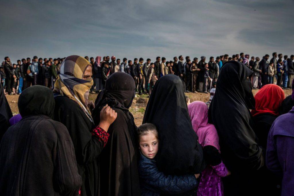 Civiles que se quedaron en Mosul durante la batalla para recuperar la ciudad del Estado Islámico esperan en línea para recibir ayuda en el barrio de Mamun (Irak), el 15 de marzo de 2017. Fotografía nominada en la categoría 'Photo of the Year' del fotógrafo Ivor Prickett.