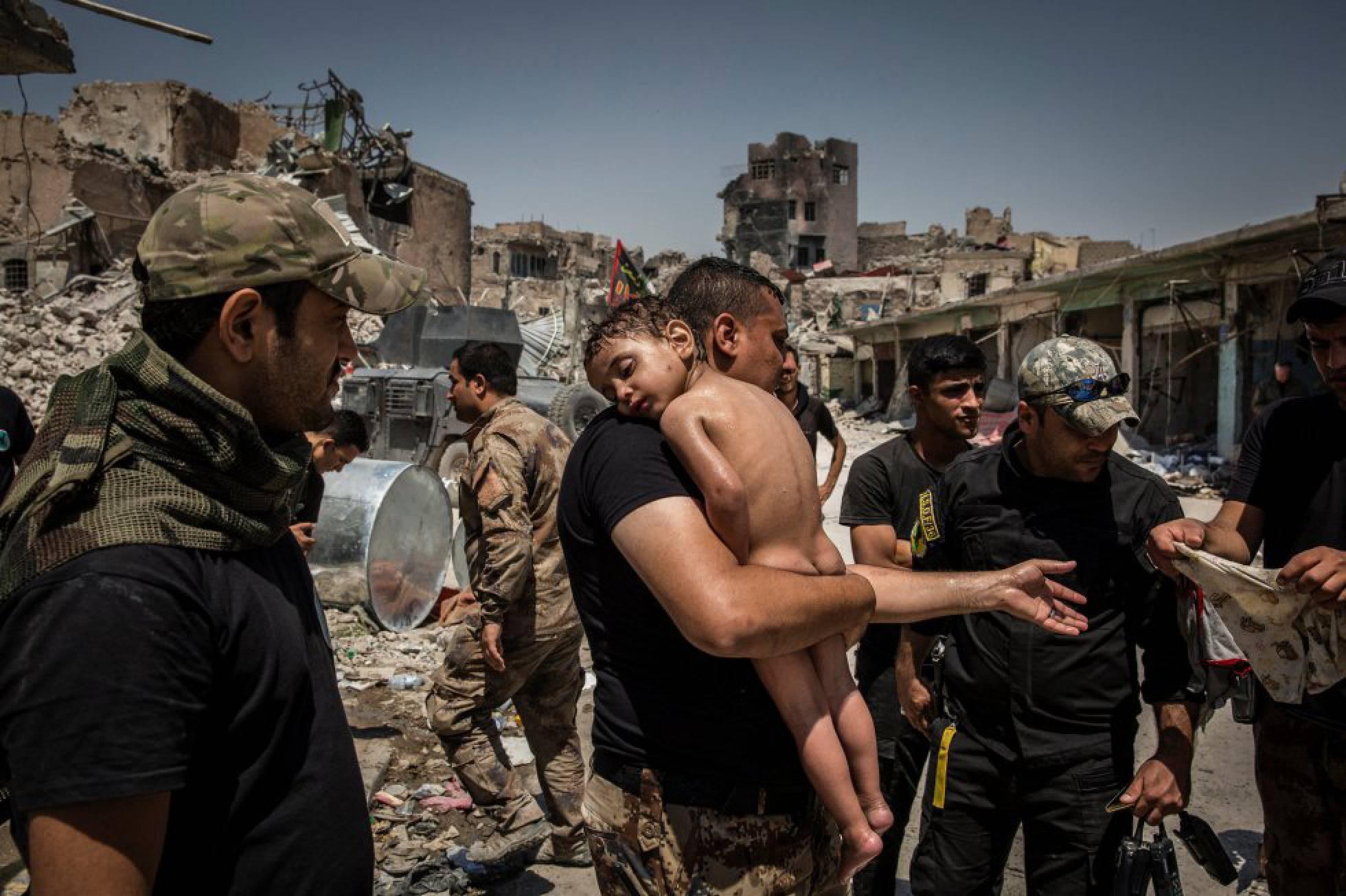 Un niño en brazos es evacuado de la última zona controlada por el Estado Islámico en la Ciudad Vieja de Mosul por un hombre sospechoso de ser militante, vigilado por soldados de las Fuerzas Especiales iraquíes, el 12 de julio de 2017. Fotografía nominada en la categoría 'Photo of the Year' del fotógrafo Ivor Prickett.